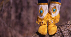 beaded and fringed mid-calf moccasins standing on log